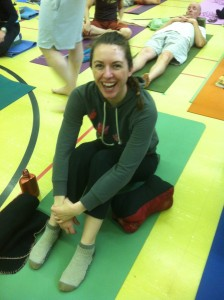 Laura laughing while sitting on her mat at the 2011 SOYA retreat