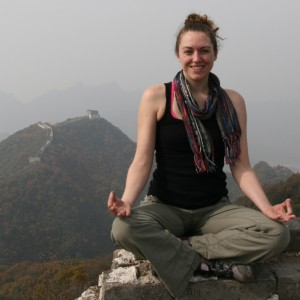 Laura sitting in easy pose on the Great Wall in China