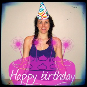 Laura wearing a birthday hat with a cake