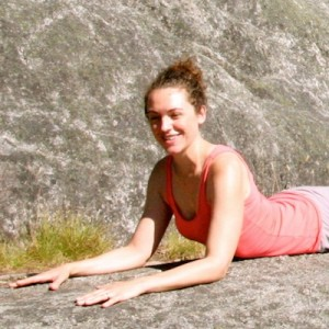 Laura holding sphinx pose on top of a big rock