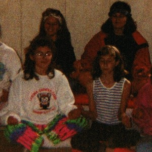 Summer campers sitting cross-legged - with Laura in neon pants!