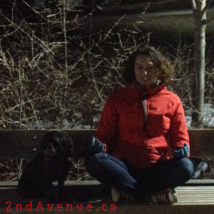 Laura sitting cross-legged on a bench, meditating at night