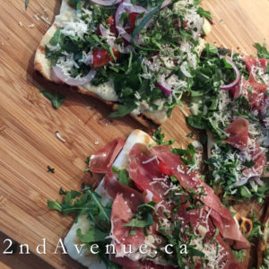 Grilled flatbread topped with arugula, red onion, basil and prosciutto